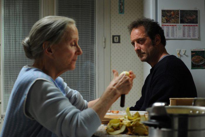 Photo d'Hélène Vincent et Vincent Lindon dans le film Quelques heures de printemps de Stéphane Brizé. les deux acteurs sont assis à une table de cuisine. Hélène Vincent épluche des pommes de terre tandis que Vincent Lindon la regarde.