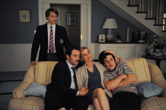 Photo d'Ernst Umhauer, Denis Ménochet, Emmanuelle Seigner et Bastien Ughetto dans le film Dans la maison de François Ozon. Les trois derniers sont assis dans un canapé à l'image d'une famille unie et le premier les observe avec un regard noir, debout et en retrait.
