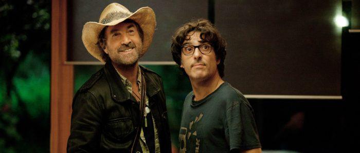 Photo de François Cluzet et Yvan Attal dans le film Do Not Disturb d'Yvan Attal. Côte à côte, les deux acteurs observent un troisième personnage et lui sourient dans une maison.