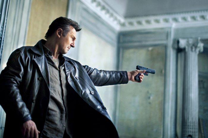 Photo de Liam Neeson dans le film Taken 3 d'Olivier Megaton. Dans un immeuble qui semble délabré, l'acteur pris en contre-plongée pointe son arme vers un ennemi.
