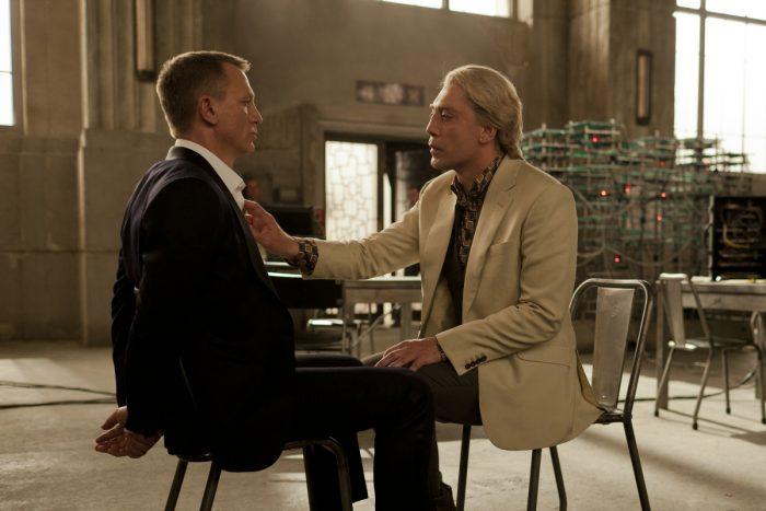 Photo de Daniel Craig et Javier Bardem dans le film Skyfall de Sam Mendes. Les deux acteurs sont face à face, assis sur des chaises. Craig est ligoté et Bardem lui touche sa chemise. Il est train de le questionner.