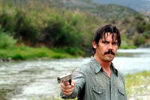 Photo de Josh Brolin dans le film No Country For Old Men des frères Coen. L'acteur sort d'une rivière et pointe son arme vers un personnage que l'on ne voit pas.