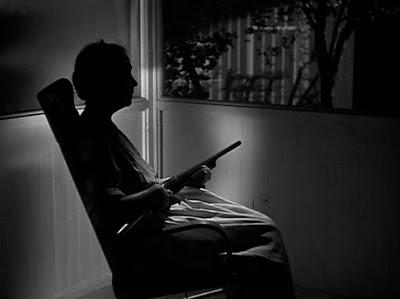 Photo de Lillian Gish dans La Nuit du Chasseur. On ne distingue pas son visage dans la nuit mais nous la voyons dans la véranda d'une maison assise sur une chaise, montant la garde avec un fusil dans les mains.