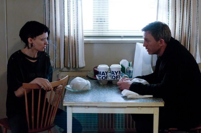 Photo de Daniel Craig et Rooney Mara dans le film Millenium, les hommes qui n'aimaient pas les femmes. Les deux personnages discutent assis près d'une table d'appartement.
