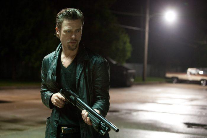 Photo de Brad Pitt dans le film Cogan : Killing Them Softly. L'acteur marche dans une rue la nuit armé d'un fusil à pompe et cherche une victime.