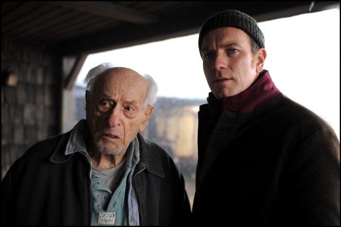 Photo d'Eli Wallach et Ewan McGregor dans le film The Ghost Writer de Roman Polanski. Les deux personnages semblent observer un élément sous un barraquement ou dans un garage.