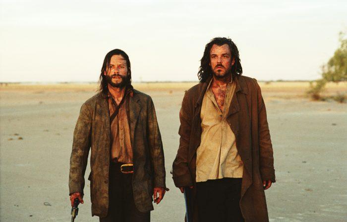 Photo de Guy Pearce et Danny Huston dans le film The Proposition de John Hillcoat. Les deux acteurs sont épuisés dans le désert. Pearce tient une arme.