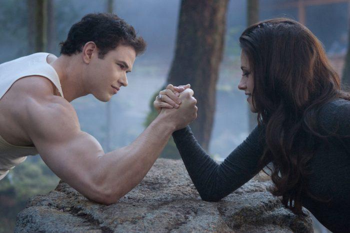 Photo de Kellan Lutz et Kristen Stewart dans le film Twilight Chapitre 5 : Révélation 2ème partie. Dans les bois, les deux acteurs font un bras de fer.