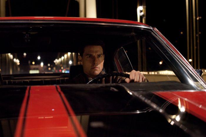 Photo de Tom Cruise dans le film Jack Reacher, dans sa voiture parcourant une ville la nuit.