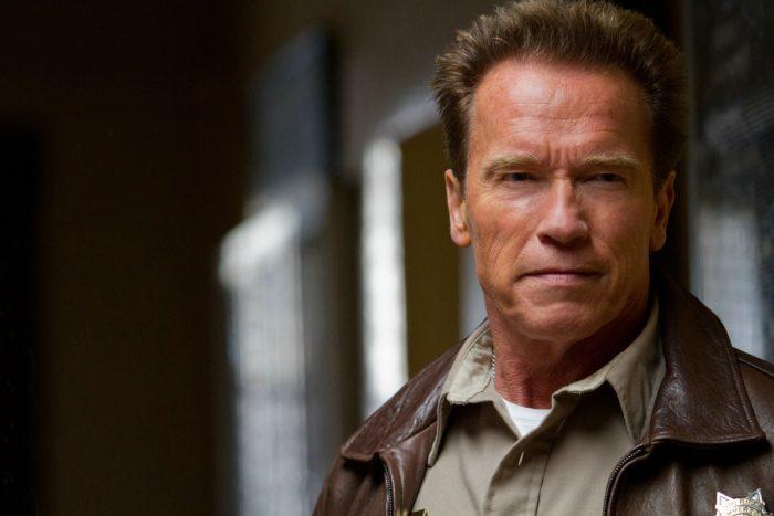 Photo d'Arnold Schwarzenegger dans le film Le Dernier Rempart. Nous voyons son buste et l'acteur affiche un air serein. Il est en tenue de shérif.
