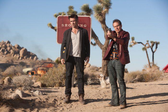 Photo de Colin Farrell et Sam Rockwell dans le film 7 Psychopathes. Dans le désert, les deux acteurs se tiennent debout face à un ennemi que Rockwell braque avec une arme.