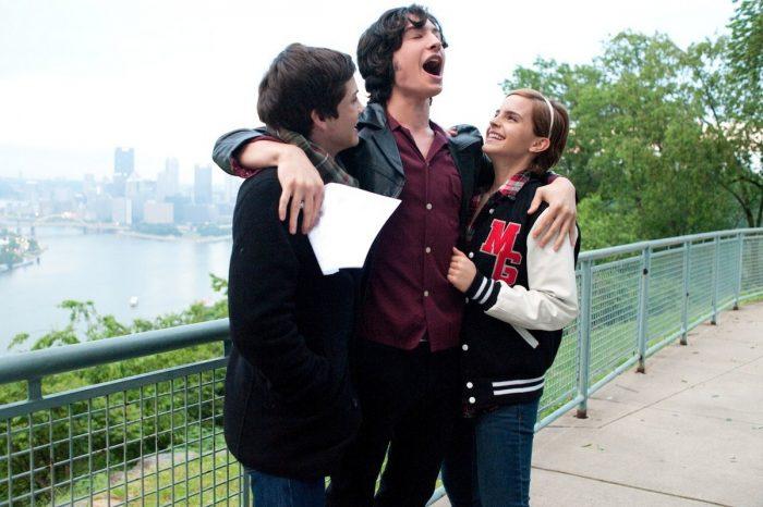 Photo de Logan Lerman, Ezra Miller et Emma Watson dans le film Le Monde de Charlie. Sur une promenade, Miller serre Lerman et Watson dans ses bras. Ils sont tous les trois euphoriques.