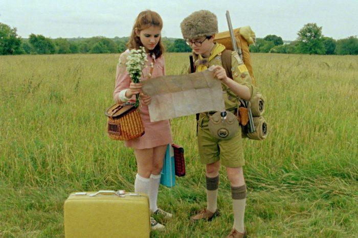 Photo des deux enfants de Moonrise Kingdom dans l'herbe en train de regarder une carte. Ils portent de nombreuses affaires et semblent être en expédition.