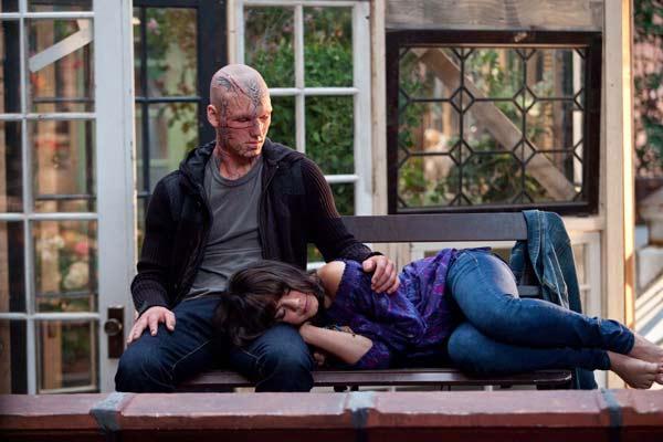 Photo d'Alex Pettyfer et Vanessa Hudgens dans le film Sortilège. Hudgens est allongée avec la tête reposant sur Pettyfer. Ils sont dans un jardin d'une maison de campagne.