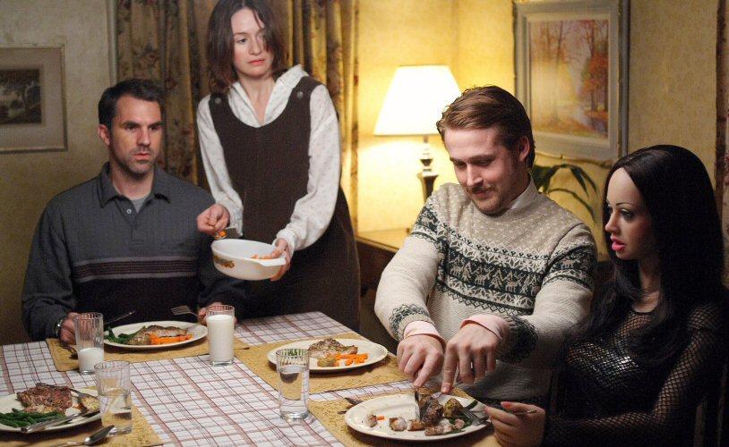 Photo de Paul Schneider, Emily Mortimer et Ryan Gosling dans le film Une fiancée pas comme les autres. A la table d'un dîner, Gosling coupe la viande de sa poupée gonflable. Les deux autres le regardent étrangement.