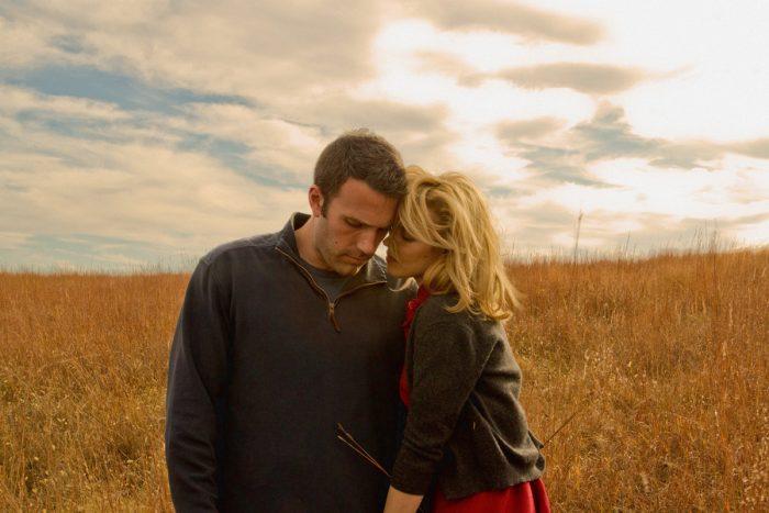Photo de Ben Affleck et Rachel McAdams dans le film A la merveille de Terrence Malick. Les deux acteurs s'étreignent dans un champ.