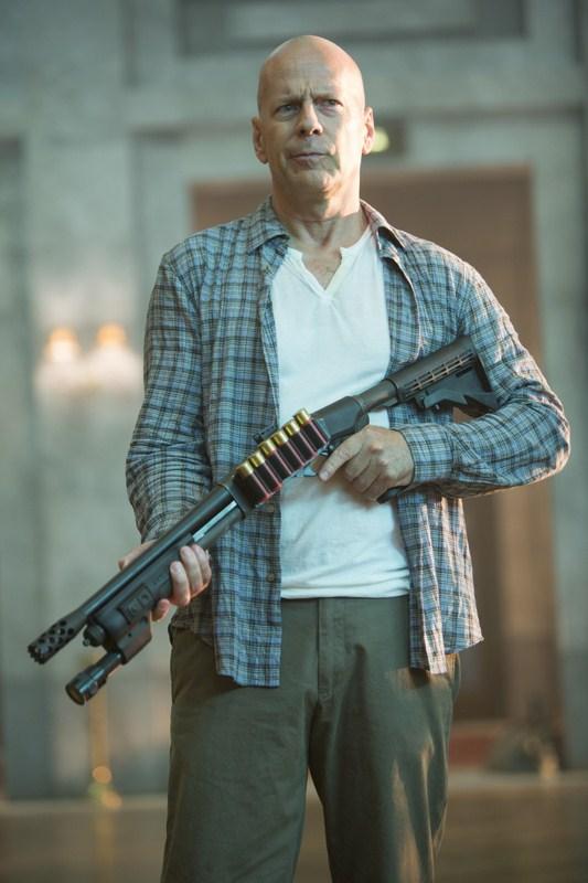 Photo de Bruce Willis dans le film Die Hard : Belle Journée pour mourir. L'acteur est debout dans un entrepôt et tient un fusil à pompe.