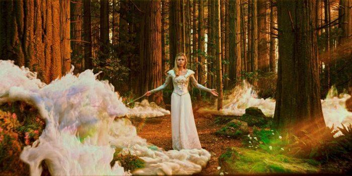 Photo de Michelle Williams dans Le Monde Fantastique d'Oz de Sam Raimi. Nous y voyons Michelle Williams en tenue de sorcière blanche dans les bois qui semble propager un sort.