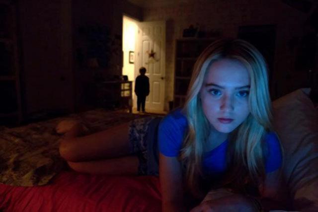 Photo de Paranormal Activity. Nous y voyons une adolescente sur son ordinateur, allongée sur son lit. Un enfant l'observe sur le pas de la porte.