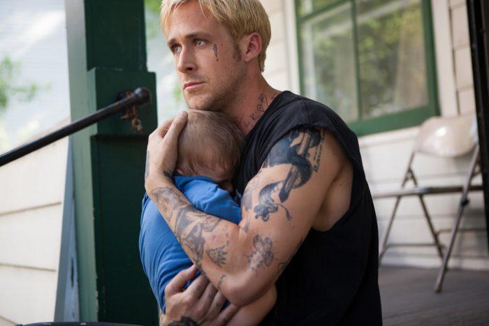 Photo de Ryan Gosling dans le film The Place Beyond The Pines de Derek Cianfrance. L'acteur est sur le perron d'une maison et tient son fils dans ses bras, le regard grave.