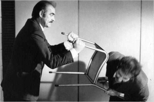 Photo de Sean Connery dans le film The Offence de Sidney Lumet. L'acteur moleste un détenu avec une chaise. Le détenu est en train de s'écrouler.