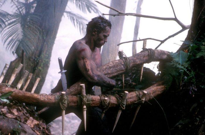 Photo d'Arnold Schwarzenegger dans le film Predator de John McTiernan. Dans la jungle, l'acteur est recouvert de boue et prépare des pièges pour lutter contre son ennemi.
