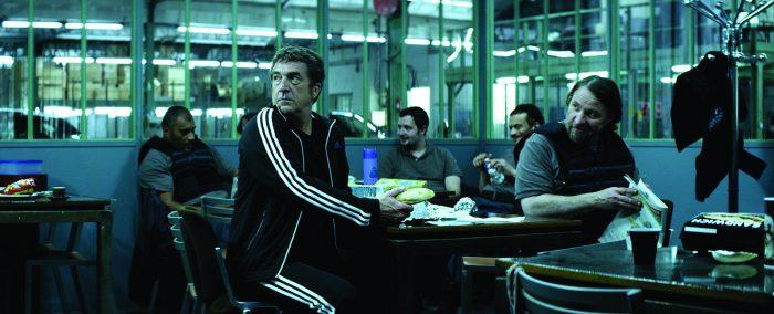 Photo de François Cluzet et Bouli Lanners assis dans l'espace de repos des convoyeurs de fond dans le film 11.6.