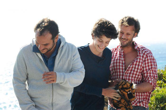 Photo de François-Xavier Demaison, Pierre Niney et Nicolas Duvauchelle dans le film Comme des frères. Les trois acteurs rient ensemble sur une falaise près de la mer.