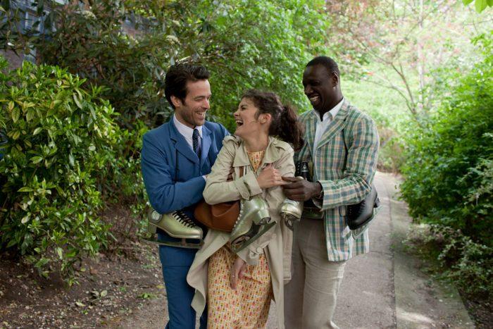 Photo de Romain Duris, Audrey Tautou et Omar Sy dans L'écume des jours de Michel Gondry. Dans un parc, les trois comédiens élégamment vêtus rient et s'étreignent.