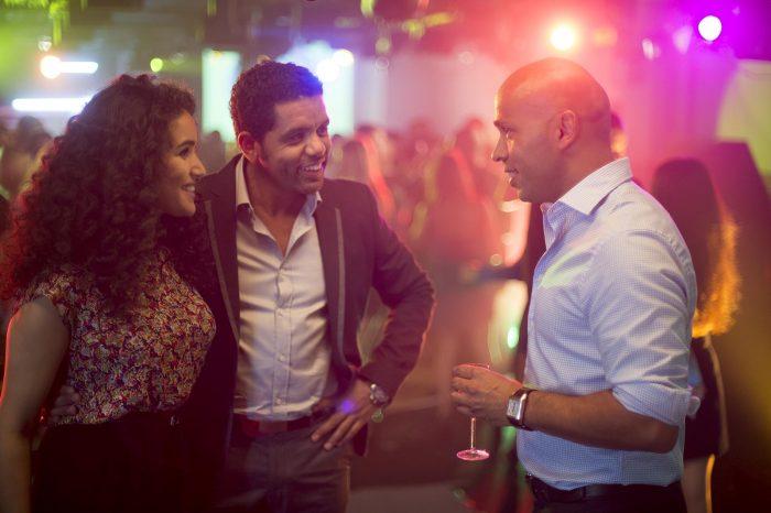 Photo de Sabrina Ouazani, Yusef Hajdi et Eric Judor dans le film Mohamed Dubois. Les trois acteurs discutent et rient ensemble dans une boîte de nuit.