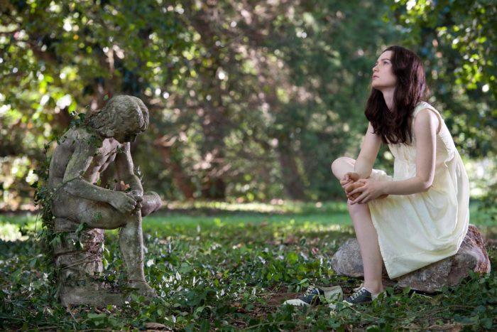 Photo de Mia Wasikowska dans le film Stoker de Park Chan Wook. L'actrice est assise dans un jardin face à une statue et effectue une pose similaire.