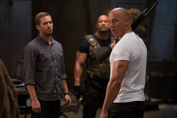 Photo de Paul Walker, The Rock et Vin Diesel dans le film Fast & Furious 6. Armés, les hommes semblent se préparer pour une mission.
