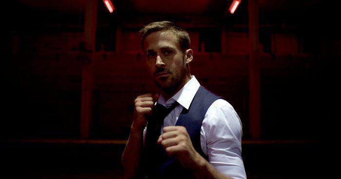 Photo de Ryan Gosling dans le film Only God Forgives de Nicolas Winding Refn. L'acteur est face à l'écran dans un pièce sombre, les poings levés, prêt à se battre.