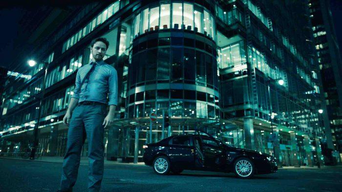 Photo de James McAvoy dans Welcome To The Punch. Dans une rue sombre près d'une voiture l'acteur est pris debout en contre-plongée et semble essoufflé.
