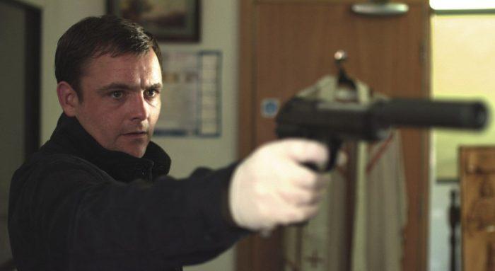 Photo de Neil Maskell dans Kill List de Ben Wheatley. Le comédien pointe un pistolet avec un silencieux vers un autre personnage dans une maison. Il porte un gant en latex.
