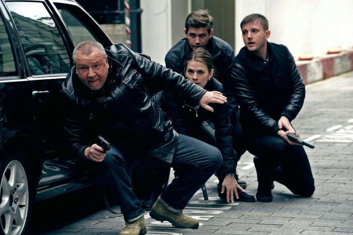 Photo de Ray Winstone, Hayley Atwell et Ben Drew dans le film The Sweeney. Quatre policiers se réfugient derrière une voiture pendant une fusillade.