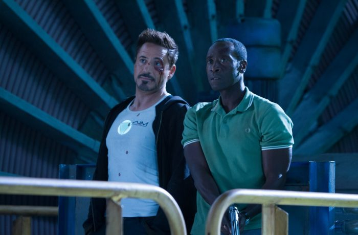 Photo de Robert Downey Jr et Don Cheadle dans le film Iron Man 3 de Shane Black. Les deux acteurs sont côte à côte et semblent faire face à un ennemi. Downey Jr saigne du visage tandis que Cheadle tient une arme.
