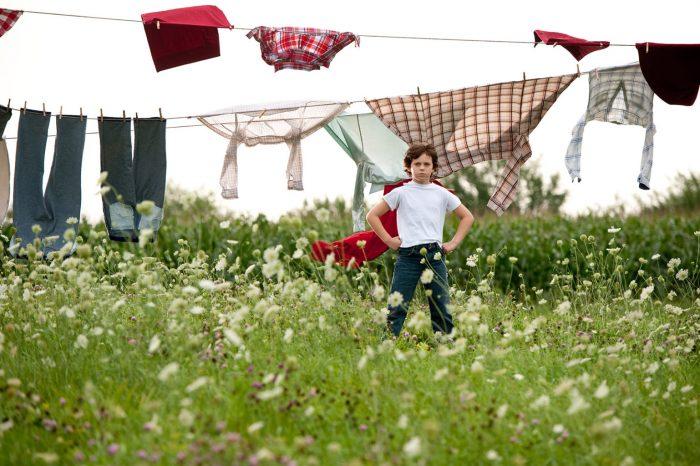 Photo de Superman enfant dans le film Man of Steel de Zack Snyder. Habillé avec une cape rouge, l'enfant se tient comme le super-héros qu'il deviendra plus tard dans un champ où du linge est étendu.