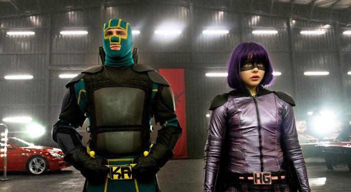 Photo d'Aaron Taylor-Johnson et Chlöe Grace Moretz dans le film Kick Ass 2. Les deux comédiens sont en tenue de super-héros dans un garage et semblent faire face à d'autres personnages.