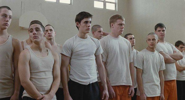 Photo d'Adam Butcher dans le film Dog Pound de Kim Chapiron. Butcher est entouré d'autres délinquants qui semblent attendre dans une salle du centre de redressement.