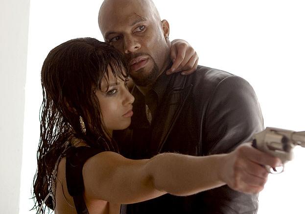 Photo d'Alicia Keys et Common dans le film Mise à prix de Joe Carnahan/ Les deux comédiens sont dans les bras l'un de l'autre et Alicia Keys pointe une arme vers un personnage que l'on ne voit pas.