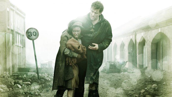 Photo de Clive Owen dans Les fils de l'homme. Tenant la femme et le bébé qu'i doit protéger, l'acteur marche dans une ville en ruines et pose sa main sur une blessure.