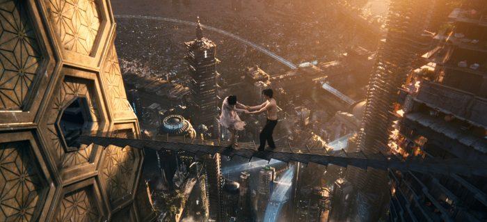Photo de Doona Bae et Jim Sturgess dans le film Cloud Atlas des Wachowski Les deux acteurs traversent une étroite passerelle au dessus d'une ville futuriste impressionnante.