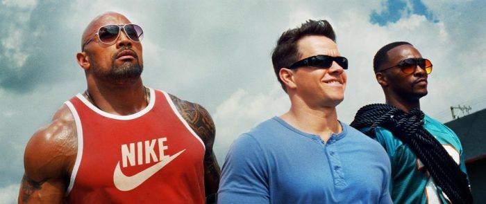 Photo de The Rock, Mark Wahlberg et Anthony Mackie dans le film No Pain No Gain de Michael Bay. Les trois acteurs marchent fièrement et sont filmés en contre-plongée.