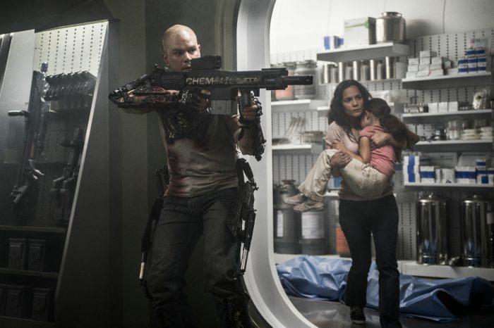 Photo de Matt Damon et Alice Braga dans le film Elysium. Dans un laboratoire, Damon pointe son arme et semble protéger Braga qui porte sa fille souffrante dans ses bras.