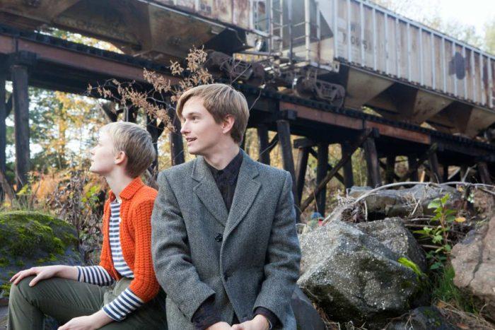 Photo de Mia Wasikowska et Henry Hopper dans le film Restless de Gus Van Sant. Les deux sont assis côte à côte sur un rocher en dessous d'un pont et discutent.