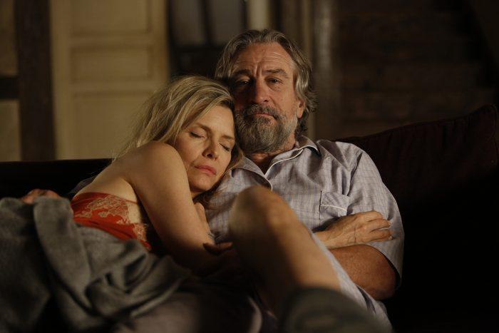 Photo de Michelle Pfeiffer et Robert De Niro dans le film Malavita de Luc Besson. Les deux comédiens sont assis dans un canapé. Pfeiffer dort dans les bras d'un De Niro penseur.