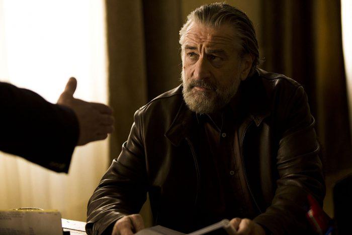 Photo de Robert De Niro dans le film Malavita de Luc Besson. L'acteur est assis et observe calmement un homme en face de lui debout qui lui tend sa main.