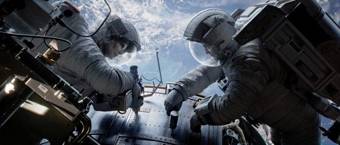 Photo de Sandra Bullock et George Clooney dans le film Gravity d'Alfonso Cuarón. En tenue de cosmonaute, les deux acteurs réparent un élément de leur navette spatiale.