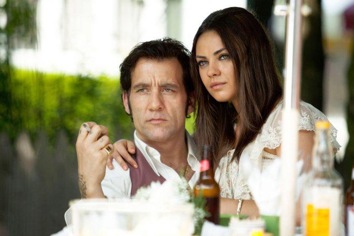 Photo de Clive Owen et Mila Kunis dans le film Blood Ties de Guillaume Canet. L'actrice est assise sur les genoux du comédien. Ils sont à une table de repas et semblent fixer un troisième personnage.